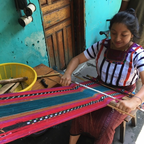Santiago Atitlan, weaving in the courtyard, she's wearing a traditional huipil, the clusters around her neck represent villages on Lake Atitlan